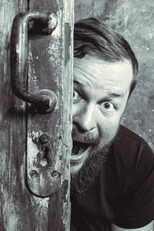 Cheerful bearded man peering out of the door