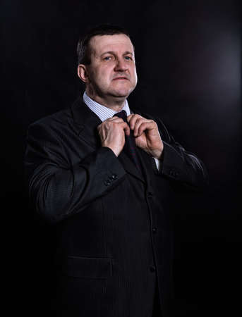 Middle aged solid man dressed in suit studio portrait Stock Photo