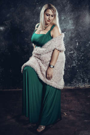 Attractive plump woman in green dress studio portrait. Stock fotó