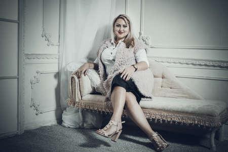 Attractive plump woman sitting on the sofa Stock fotó