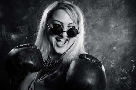 Attractive plump woman with boxing gloves studio portrait.