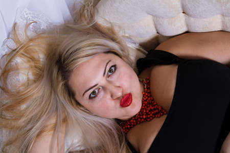 Attractive plump woman laying on sofa