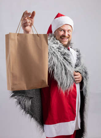Cheerful Santa dressed in fur skin offering a present Stock Photo