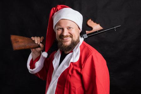 Cheerful Santa with machine gun studio portrait