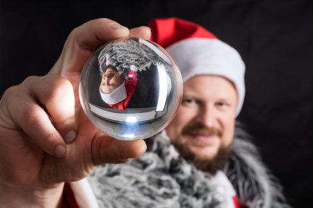 Cheerful Santa dressed in fur skin with crystal spehre