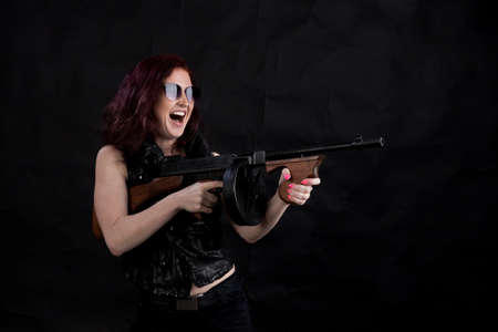 Beautiful woman dressed in black jacket with a gun Imagens