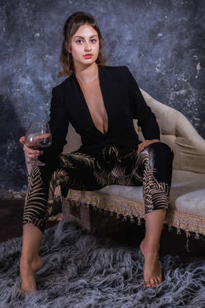 Beautiful young lady in black dress sitting on sofa with glass of wine Stock fotó