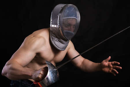 Matured man with naked muscular torso in fencing helmet and epee