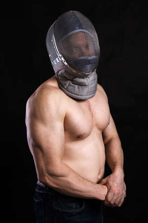 Matured man with naked muscular torso in fencing helmet