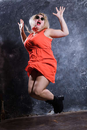 Attractive plump woman in red dress jumping