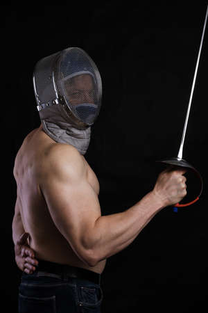 Matured man with   muscular torso in fencing helmet and epee