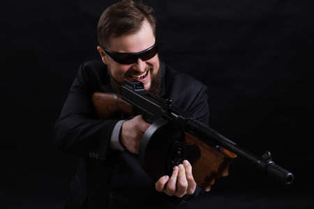 Mature bearded man in sunglasses dressed in suit with tommy gun