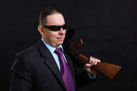 Mature gangster in sunglasses dressed in suit with tommy gun