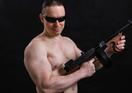 Mature man in sunglasses and naked torso with tommy gun