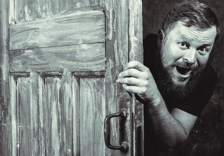 Cheerful bearded man peering out of the door Standard-Bild