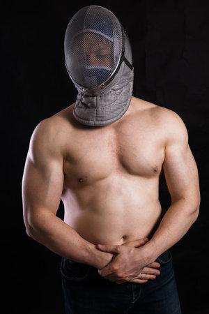 Matured man with   muscular torso in fencing helmet