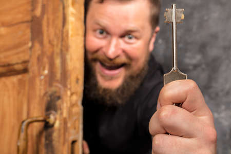 Cheerful bearded man with key peering out of the door