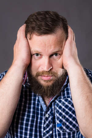 Frustrated bearded man holding his head by two arms