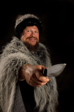 Bearded hunter dressed in a fur mantle and fur hat with knife Banque d'images