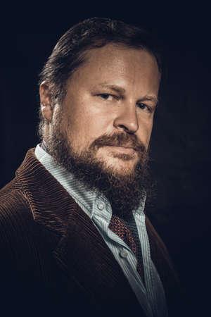 Stylish bearded man dressed in suit studio portrait on black background.