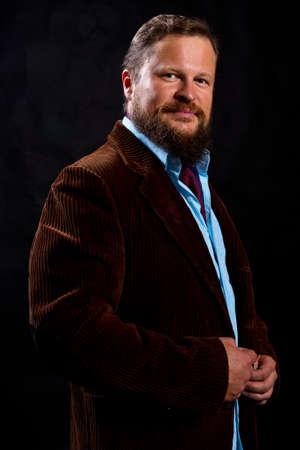 Stylish bearded man dressed in suit studio portrait on black background. Foto de archivo