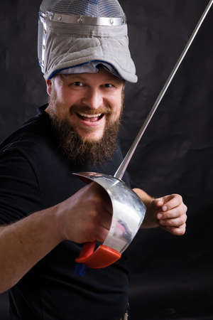 Middle aged bearded man with epee and helmet