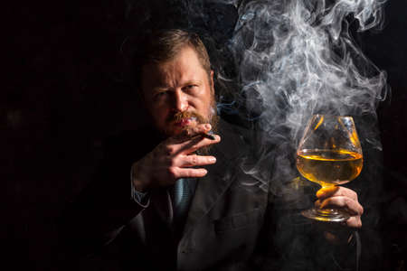 Solid confident bearded man in suit with glass of whisky and cigar with fume Banque d'images