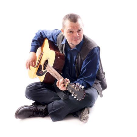 Mature musician plays acoustic guitar emotional studio portrait on white background. Фото со стока