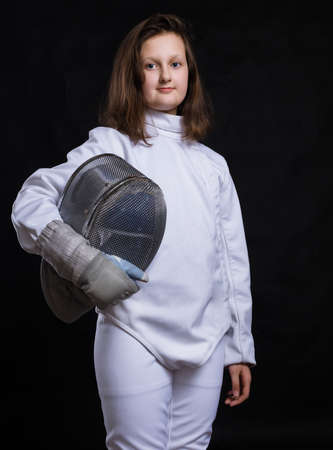 Teenage girl fencer dressed in uniform with epee and helmet