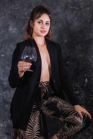 Beautiful young lady in black jacket with glass of wine