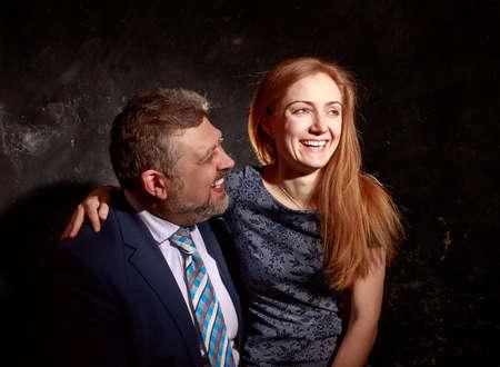 Bearded man and young woman, happy couple studio portrait 免版税图像