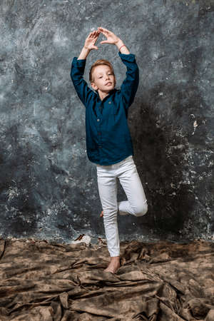 Young dancer dressed in white jeans and blue shirt doing figures studio portrait