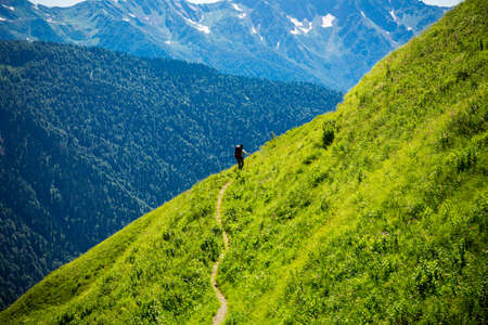 Beautiful mountain landscape with tourists hiking at Caucasus mountains