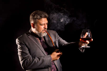 Solid confident bearded man in suit with glass of whisky smoking pipe