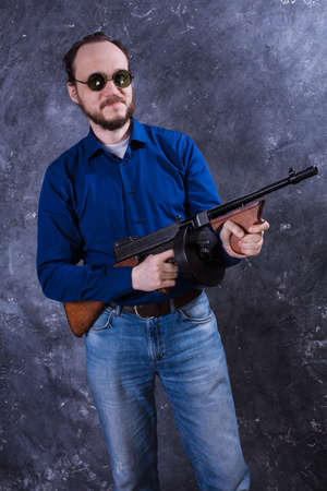 Mature man in sunglasses with tommy gun