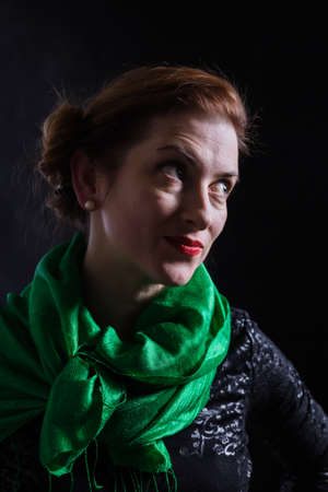 Beautiful lady in neckerchief studio portrait on black background.