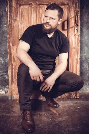 Mature bearded man sitting on vintage door background Reklamní fotografie