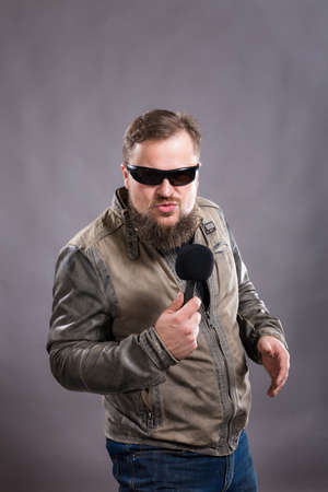 Bearded emotional rock singer with microphone studio portrait.