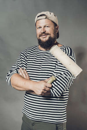 Joyful bearded foreman with brush roller studio portrait