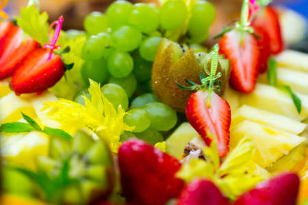 Served tasty fruits on dish in restaurant close up view.