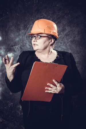 Middle-aged woman construction superintendent in helmet studio portrait.