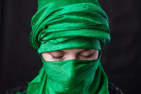 Beautiful muslim woman dressed in green headscarf