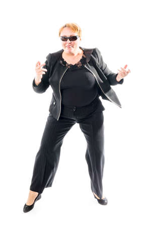 Middle aged woman in black jacket and trousers dancing an emotional dance Stock Photo - 164672134