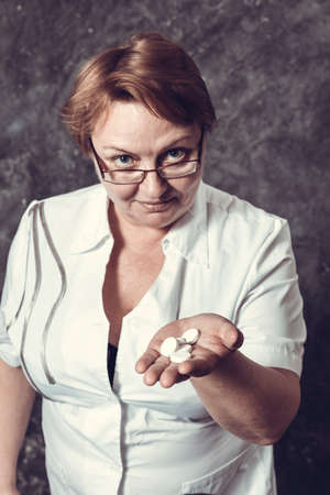 Middle aged woman pharmacist in medical robe offers the tablets