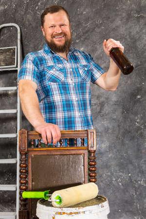 Joyful bearded foreman has a break with bottle of beer