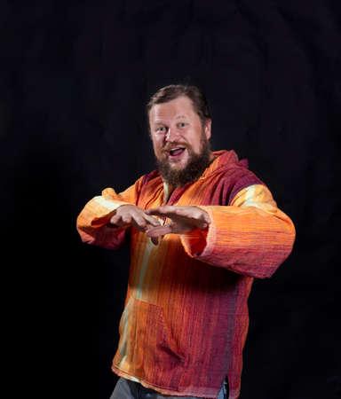 Joyful bearded man in bright orange shirt dancing