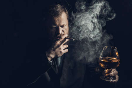 Solid confident bearded man in suit with glass of whisky and cigar with fume
