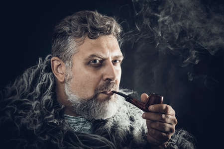 Solid bearded man in a fur mantle smoking pipe