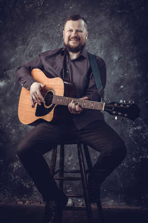 Mature musician plays acoustic guitar emotional studio portrait.