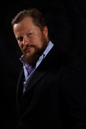 Thoughtful solid bearded man dressed in suit Foto de archivo